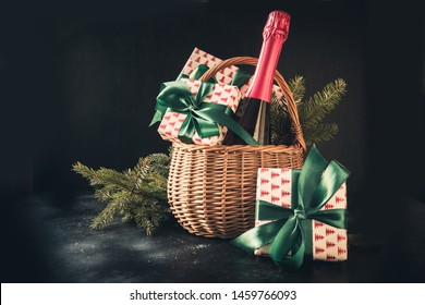 Christmas gift hamper with champagne and gift on black. Space for your greetings. Xmas.