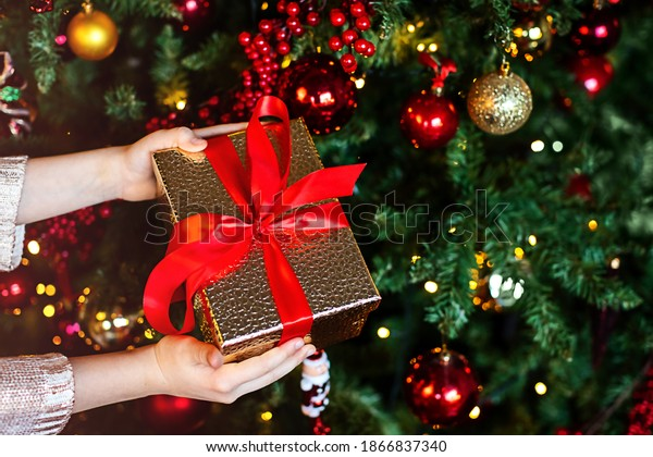 Christmas gift in the hands of a child on the background of a decorated Christmas tree