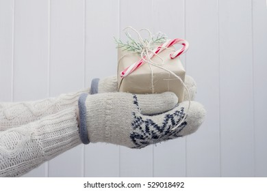 Christmas gift in hands in mittens on white