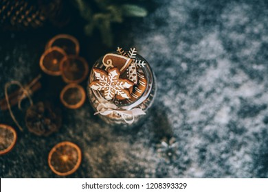 Christmas gift with homemade gingerbread cookies, nuts and chocolates. Glass jar, fir branches, Christmas spices and decor. Winter holidays, New Year or Christmas concept. Top view with copy space.