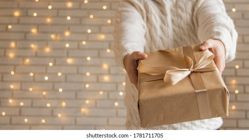 Christmas gift in man hands holiday wallpaper poster concept picture with white wall background and garland illumination lamps  - Shutterstock ID 1781711705