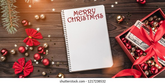 A Christmas gift, money packed with red slack, Xmas items, on a wooden background. Top view. Text space in the notebook. Light effect.