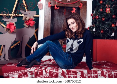 Christmas Gift. New year celebration. Beautiful holday decorated room with Christmas tree with presents under it. New Year and Christmas concepts. Beautiful girl sitting near New Year tree.
