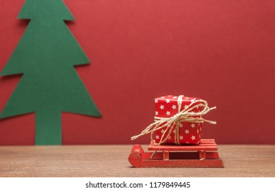 christmas gift on small sledge red background