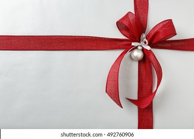 Christmas gift Christmas present background with silver wrapping paper and red bow