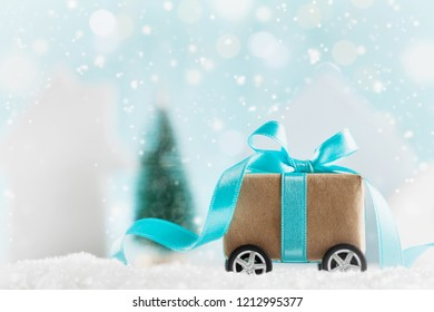 Christmas gift or present box on wheels against turquoise bokeh background. Holiday greeting card with snow effect.