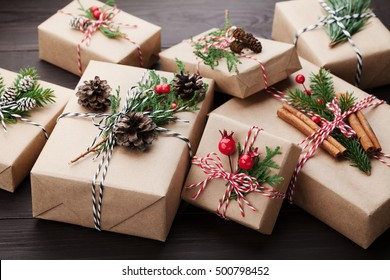 Christmas gift or present box wrapped in kraft paper with decoration on rustic wooden background.