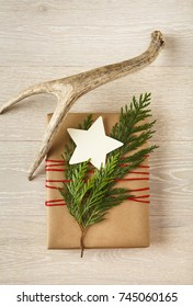 Christmas gift present with recycled wrapping paper, natural evergreen decorations, a blank gift tag and deer antlers on wood background. Simple, modern, country style holiday decorations.