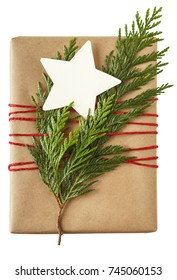 Christmas gift present wrapped in recycled wrapping paper with natural evergreen decorations and a blank gift tag. Simple, modern, country style holiday decorations isolated on white background.