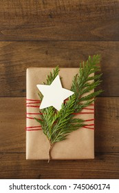 Christmas gift present wrapped in sustainable recycled wrapping paper with natural evergreen decorations & blank gift tag on rustic wood background. Simple, modern, country style holiday decorations.