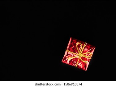 Christmas gift in red paper isolated at black background. Gift box.