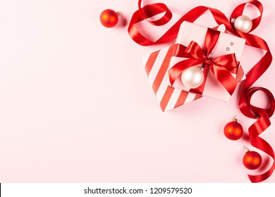 Christmas gift with red ribbon on pink background with decorations. Beautiful holiday composition. Background with copy space.