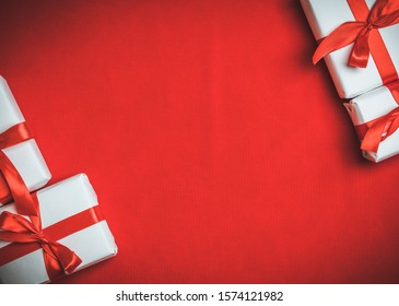 Christmas gift with red ribbon on the red background. Christmas and New Year background.