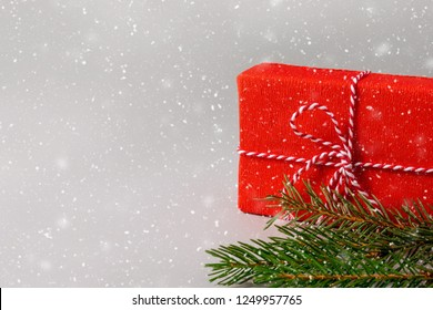 Christmas gift in red wrapping paper and green spruce branches under snow on grey background with copy space