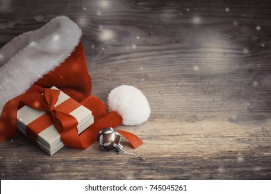 Christmas Gift with santa hat and christmas decoration on wooden background - Shutterstock ID 745045261