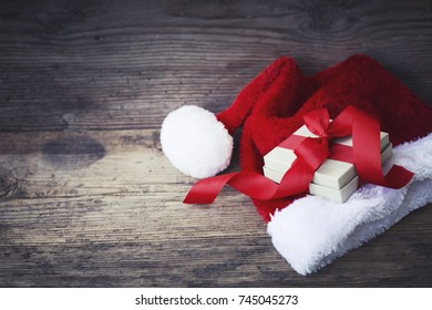 Christmas Gift with santa hat and christmas decoration on wooden background - Shutterstock ID 745045273
