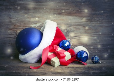 Christmas Gift with santa hat and christmas decoration on wooden background - Shutterstock ID 745045297