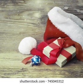 Christmas Gift with santa hat and christmas decoration on wooden background - Shutterstock ID 745045312