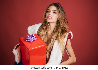 Christmas gift. Sexy santa claus girl isolated on red background. Excited woman in red santa claus outfit holding present. Christmas and new year concept.
