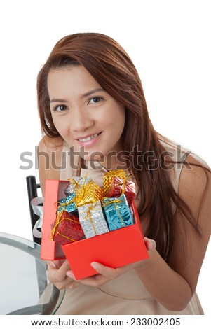 5b6ad89a8ffee Happy excited santa woman showing christmas present. Christmas shopping  woman holding many Christmas gifts in her hand wearing santa hat.