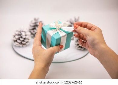 A Christmas gift. Women's hands hold a small jewellery box with a white ribbon. Cones on the background.