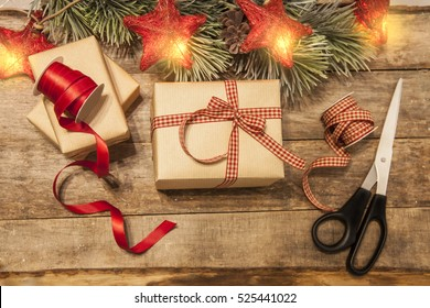 christmas gift wrapped in checked ribbon and craft paper with scissors red ribbon reel