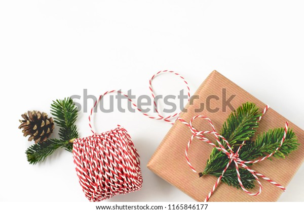 Christmas gift wrapped in craft brown paper and decorated with fir-tree branches isolated on whote background. New year gift giving concept. Free copy space.