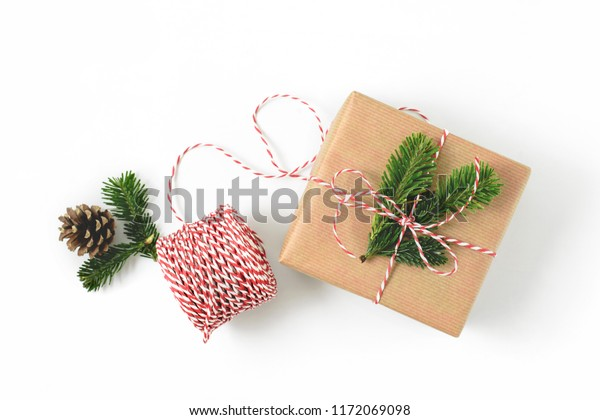 Christmas gift wrapped in craft brown paper and decorated with fir-tree branches isolated on whote background. New year gift giving concept.