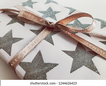 Christmas gift wrapped in paper with silver glitter stars and decorated with a festive Merry Christmas ribbon tied in a bow. Close-up high angle view on a plain background