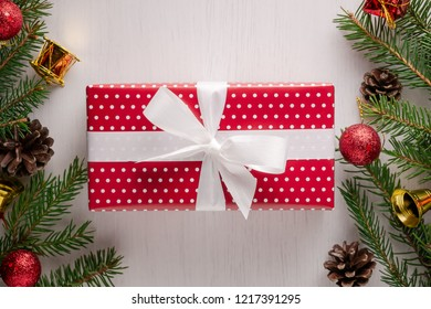 Christmas gift wrapped in red paper with white polka dots and big white bow, surrounded by spruce twigs, pine cones and red and golden decorations. Flat lay style