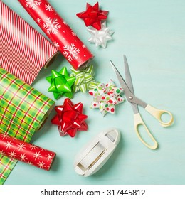 Christmas Gift Wrapping Party Time with Colorful Paper, Ribbon Bows, Scissors and Tape on Cyan Blue Shabby Chic Wood Board Background with Square Crop and Room or Space for copy, text, your words.