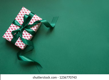 Christmas giftbox with green ribbon on green surface. Space for wishes. Holiday card. Top view.