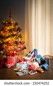 Christmas gifts for all family under decorated tree with lights and colorful baubles.