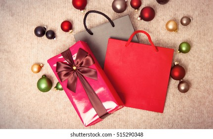 Christmas gifts and baubles with shopping bags on knitted background