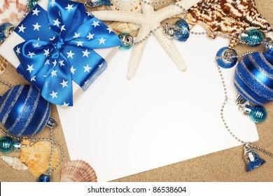 Christmas gifts and blank card on sand beach,closeup.