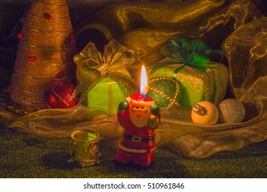 Christmas gifts in boxes. boxes tied with ribbons with bows. A green box. The colorful balls. The candle is burning. Santa Claus in the foreground. For design, postcard, Wallpaper. Shades of green.