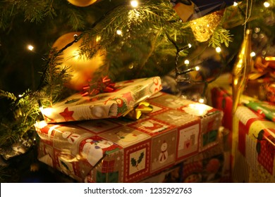 Christmas gifts brought by Santa Claus lying under the lit Christmas tree. Traditional Polish Christmas Eve evening