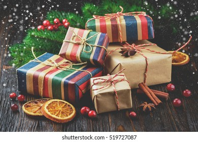 Christmas gifts, cinnamon, anise stars, cranberries berries and spruce branches on a wooden background