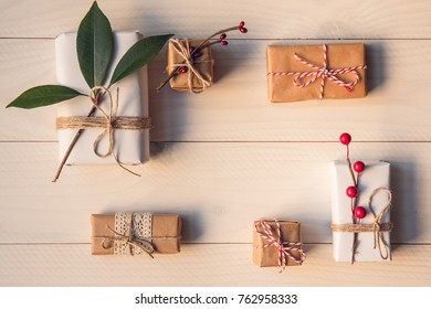 Christmas gifts decorated by festive decor on white wooden table. Christmas and celebration concept. Toned with old style sepia colors. Top view.