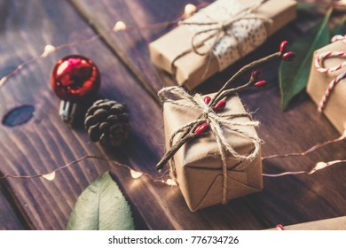 Christmas gifts decorated by festive decor over brown wooden table. Dark rustic style. Toned with soft sepia old fashioned colors. Christmas and celebration concept.