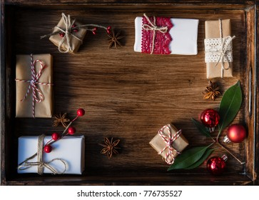 Christmas gifts decorated by festive decor on old brown rustic wooden table. Christmas and celebration concept. Toned with old style sepia colors. Top view.