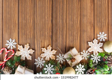 Christmas gifts, Christmas decorations, Christmas cookies, tree branches and snowflakes on a wooden background. Flat lay style