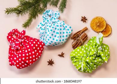 Christmas gifts furoshiki on pink background. Eco christmas holiday concept. Flat lay top view.