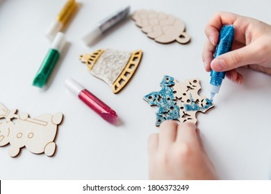 Christmas gifts. handmade Wooden toys.Making New Year decoration. Christmas ornaments. little child making Christmas decoration ornament .concept of creativity, handwork, preparation for the holiday. - Shutterstock ID 1806373249
