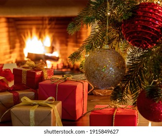 Christmas gifts interior home celebration concept. Xmas silver gold ball, tree branch, Santa Claus doll, gift boxes with ribbons, burning fireplace background. Warm family moments.