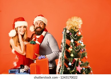 Christmas gifts and love concept. Santa and sexy girl with xmas gift boxes. Man with beard and woman with happy faces on red background. Mister and Missis Claus with red and blue presents near tree