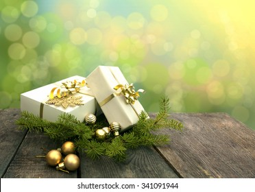 Christmas gifts on a simple table with fir tree branches and balls. Bokeh background with space for your text