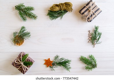 Christmas gifts on a white wooden background with sprigs of spruce, Christmas tree. New Year gifts