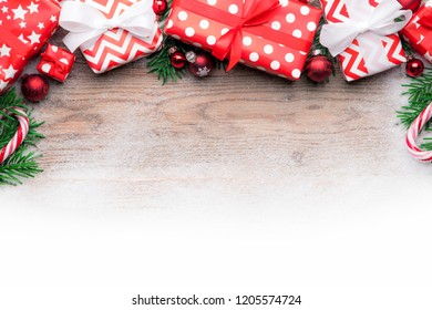 Christmas gifts on wooden background table with snow and baubles