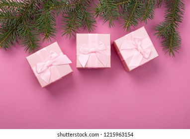 Christmas gifts with pink ribbon on pink pastel background with festive decorations. Christmas background with copy space.
